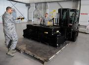 Master Sgt. Chris Eggleston, section chief small air terminal, Tech. Sgt. Peter Little, noncommissioned officer in charge of air freight, and Staff Sgt. Benjamin Woods, air freight supervisor, of the 6th Logistics Readiness Squadron, prepare to load Spanish coins onto an aircraft at MacDill Air Force Base.