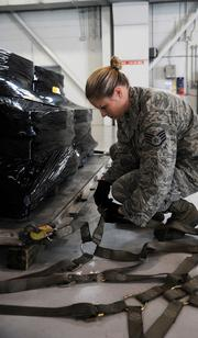 Staff Sgt. Rachael McCray, 6th Logistics Readiness Squadron Mobility Training Instructor, connects a cargo net to a pallet of Spanish coins to be loaded on a Spanish C-130 at MacDill Air Force Base.