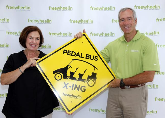 Christine Burdick, left, president Tampa Downtown Partnership holds the 'Pedal Bus Crossing' sign that Dr. Scott Latimer, market president of Humana of Central Florida, donated at Humana's Freewheelin event at the Republican National Convention August, 26, 2012 in Tampa.