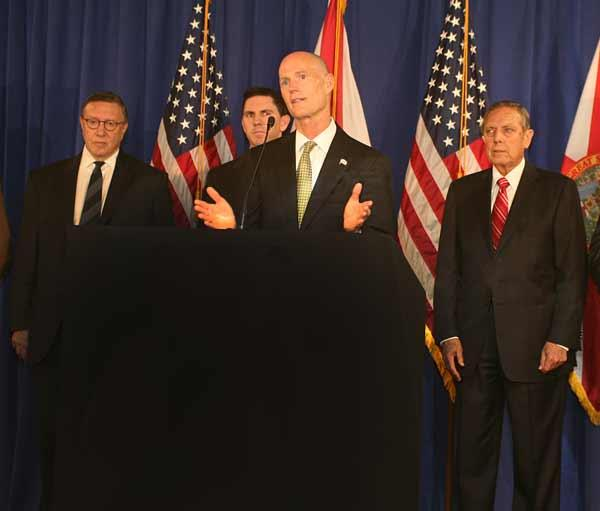Gov. Rick Scott speaks of his mission to grow Florida jobs during a press conference to announce a partnership between the Tampa Bay Host Committee and Bloomberg LP. Behind him left to right are Bloombrg Chief Content Officer Norman Pearlstine, Tampa Bay RNC Host Committee President and CEO Ken Jones and former Florida Gov. Bob Martinez.