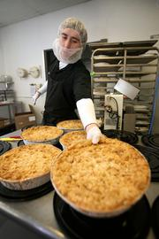 David Aristizabal, kitchen supervisor, prepares to cut apple crisps and stack cheesecakes.