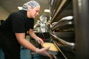 Mallory Osborne, kitchen staff, removes cheesecakes from the rack.