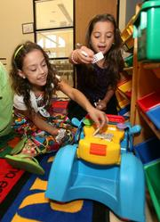 Playing at Kid's Korner at the Children's Board of Hillsborough County in Tampa are Anneliese Cotronero, left, with Cristiana Cotronero.