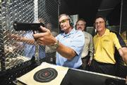 Dave Sylvester, chief project officer, Kevin Lothridge, CEO, and David Epstein, COO, on a mobile firing range used for ballistics training.