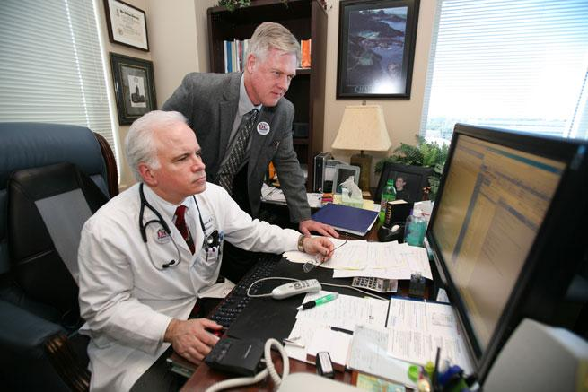 Using EMRs at Diagnostic Clinic Dr. James F. Rivenbark III, standing, confers with Dr. Michael Thompson on a patient issue.
