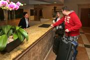 At Sheraton Sand Key Resort, Migena Zelka helps guests Oliver and Anna Runschke check out.