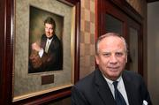 Bob Covington, president of Palm Bank, with a portrait of Gene Langford, founding chairman of the board who passed away last year.