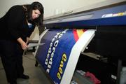 A RoadSigns Company, DBA, Now That's A Wrap! Krista Straub, art director, checks a job coming off a large format printer for a PSTA bus.