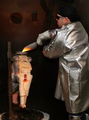 Keny Siebens, casting tech, with a 2100 degrees F mold in the casting furnace.