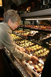 Susie Kleyweg, restaurant trainer at Cooper's Hawk Winery, stocks the candy case. All candy is made in-house daily in the tasting room.