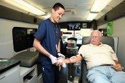 Roy Bertke, director of Florida Blood Services, gets his blood taken by Moises Rodriguez, phlebotomist.