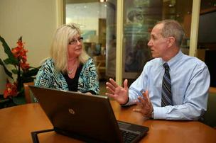 Client Beverly Blakely speaks with Roy Hellwege, president and CEO of Pilot Bank, about programs focused on the health care community, in the bank's Westchase branch.