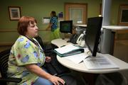 Nurse Sherry Raser works at an All Children's nursing station with electronic health records.