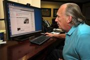 Chris Hoyer reviews the Flat Rock Systems website in his office.