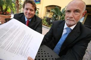Rick Tutwiler, senior executive associate, and Dick Tutwiler, president of Tutwiler & Associates, with an insurance policy form in downtown Tampa.