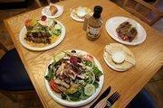 Greek salad, souvlaki chicken skewers, rice and pita bread with tzatziki sauce and gyro sandwich at the Little Greek Restaurant.
