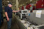 Bob Tuell, senior process technician, working coupons after the press run at Valpak in Largo.