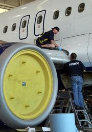 Robert George and Seth Funderburg, aircraft technicians, working on an Airbus 320.