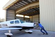 NAFCO and plane hangar at 3907 Aero Place in Lakeland.  Suresh Baichulall, hanger owner and pilot at hangar moving a Piper Cherokee 150.