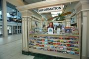 Michele Routh, community and media relations director, stocks the visitor information booth with brochures.