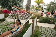 Sheetal Patel from Tampa lays in a hammock eating lunch outside her room at Postcard Inn On The Beach at St. Pete Beach.