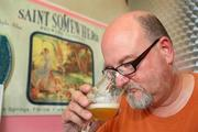 Bob Sylvester, owner and head brewer, checks the beers taste and smell.