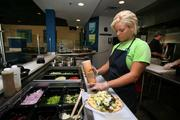 Mo'Ziki, Greek-inspired restaurant in Largo. Chanel Montchal, counter, making a Mo' Pita sandwich.