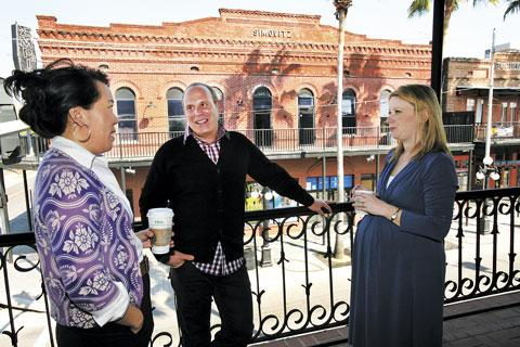 Randy Rosenthal and his wife, co-owner and partner of Tricycle Studios, Tona Bell, left, visit with Kim Francis, right, owner of Kim Francis Communications, who moved her office to Ybor five months ago.