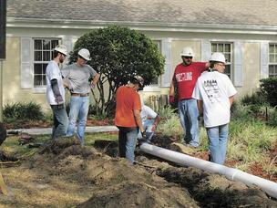 PCL Civil Constructors' volunteers work during the United Way Day of Caring to install a drainage pipe at the Children's Home in Tampa.