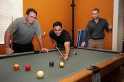 Lancet Indemnity's Stephen Maniscalco, premium finance manager and Brian Menendez, VP of business development playing pool with Uhsome's Chris Arnoldi, CEO and founder, at the Uhsome office.