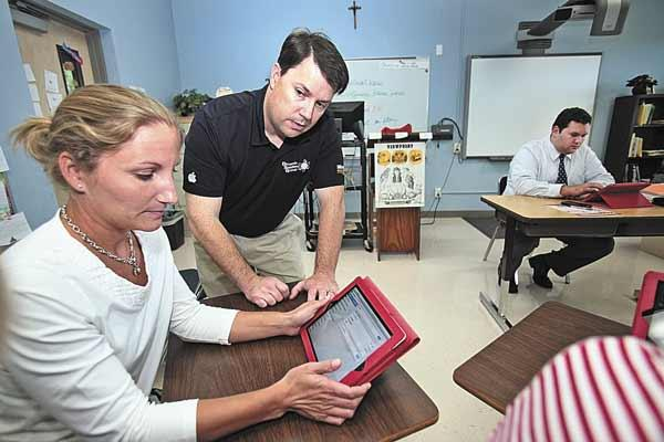 Dynamic Solutions Group Inc.'s Jim Watt, president and CEO, standing, works with faculty and middle school teachers at Our Lady of Lourdes Catholic School in Dunedin. Teacher Christine Bahret gets instruction from Watt in a technology integration class .