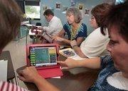 Teachers, Patrick Durkin, Jean Brown, Mary Gross, Nancy Casalino work on iPads at Our Lady of Lourdes Catholic School in  Dunedin.