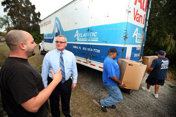Bob Glenn, vice president and general manager of Atlantic Relocation Systems, center, talks with client Victor Morales, who is moving from Clearwater to Georgia. Movers are Frank Muguercia, crew chief, and his brother, Al Muguercia.