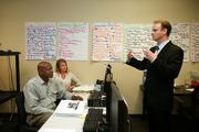 TruGreen's Jeff Walter speaks to outbound sales training class attendees, Harold Bentley and Micki Baker.