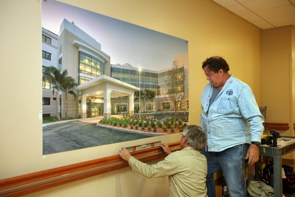 At St. Anthony's Hospital, Paul Ketchum and Brian Petersen with Architectural Signage Systems Inc., based in Lutz, install a team-member art project.