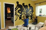 Jair Medina and Timothy Innamorato, with Splat Paint, painting a mural in one of the bedrooms at The Parade of Homes.