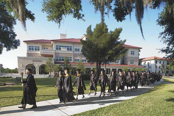 2012 graduates processing to commencement ceremony, with the new building for the Donald R. Tapia School of Business in the background.