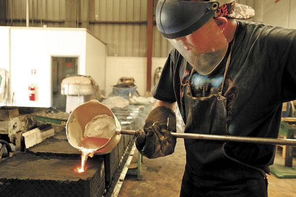 Kevin Hammer, foundry production for Creative Sign Designs, handles melted aluminum and pours it in forms. A 1,600-degree furnace melts aluminum rims to be used in making sand cast aluminum parts.