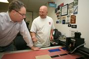 Jamie Harden, president and CEO of Creative Sign Designs, watches as Dave Menard, interior sign production, engraves ADA signage.