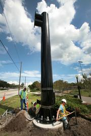 Highway Safety Devices Inc.  along Hwy 60 in Clearwater. Danny Trigg, ITS inspector for Pinellas County (standing above ground) inspects while Michael O'Brien, lead man for Highway Safety Devices Inc, (middle) and Justin Worthington, laborer, (right) works a job installing pipe for power and fiber for a DMS board.