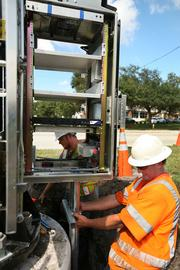 Highway Safety Devices Inc.  along Hwy 60 in Clearwater. Travis Young, project foreman (orange vest) and Michael O'Brien, lead man (yellow vest and little beard) for Highway Safety Devices Inc, work a job installing pipe for power and fiber for a DMS board.