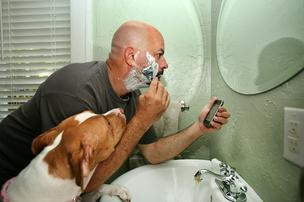 Art Fyvolent, CEO, Ideas4, shaves and gets ready for work while working on his iPhone. His pit bull, Bella, hangs out in the bathroom with him.