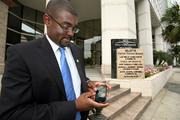 Brian Lamb uses his iPhone outside his Fifth Third office in downtown Tampa. He works on his laptop at his office.