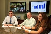 Sabal Trust Co. Bill McQueen, president, (head of table in white shirt and blue striped tie) leads the monthly meeting between four office branches using the large flat-screen. With him is Larry Fasan, executive VP and Christy Meisiek, relationship manager.