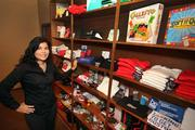 Janice Rodriguez, founder and president of Adelante Live Inc.,  stands at their wall of promotional items that are examples of items their talent hands out at promotions and demos.