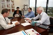 James Olson, principal/CMO, Manish Gupta, principal/CTO, Mike Gottfried, principal/COO and Pete Kirtland, President, gather around a table at ASPire Financial Services