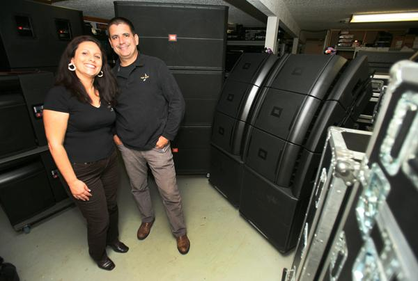 Coda Sound's Maritza Astorquiza, co-owner and managing partner, and Alex Cora, producer/master engineer, with sound equipment and instruments ready for an event.