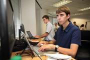 MITRE's Andrew Schreiber, software applications developer engineer, writing code for a project with intern, Robert Clark, Center for Advanced Technology in St. Pete.