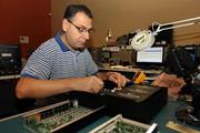 Engin Calik, engineering tech, in the engineering test lab, working on an integrated multi-room audio solution at Clare Controls.