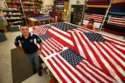 Flags Unlimited Inc. Kevin Lynch, marketing coordinator, in production with a 12 X 18 ft. flag just finished for a local car dealer.